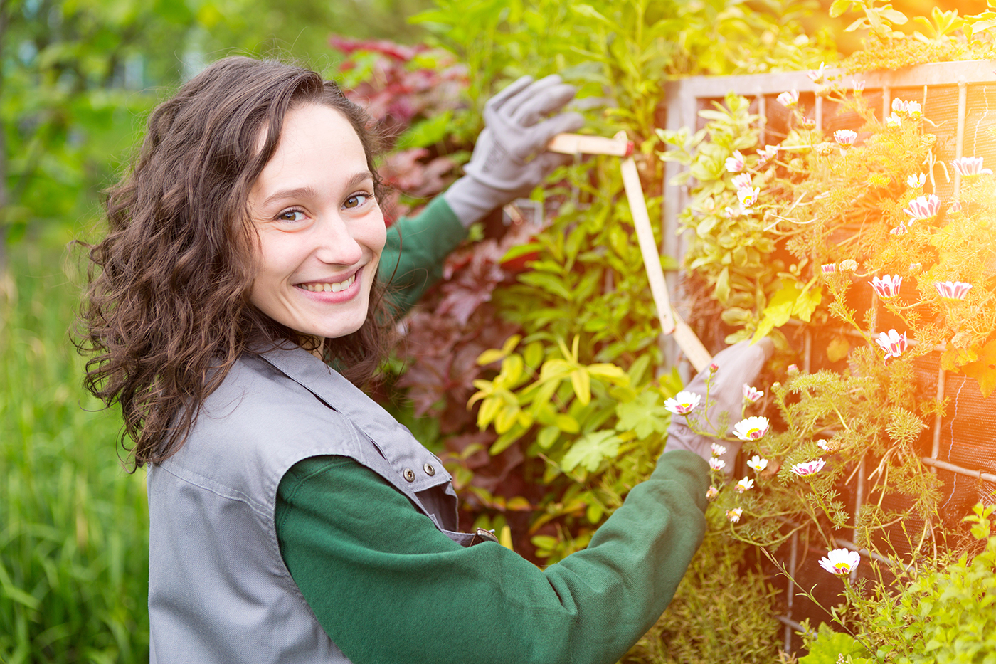 View of a Young attractive landscaper woman working in a public park